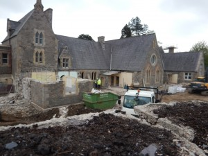 Photo showing rear of building during works - playground has been removed and building is being prepared to receive new classrooms